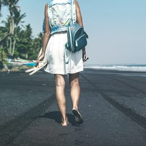 Young woman on a black sand beach, Bali island. Indonesia.