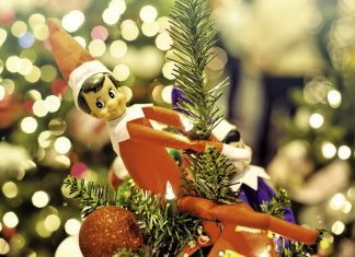 Elf on the Shelf perched on top of a Christmas tree